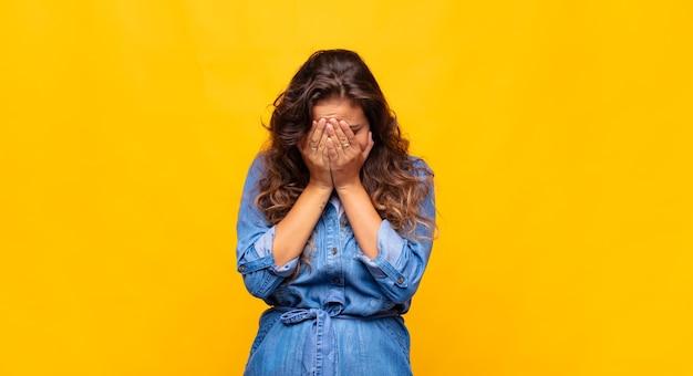 Молодая выразительная женщина позирует на желтой стене