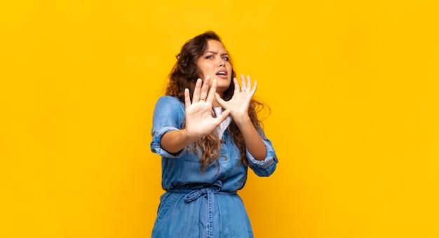 노란색 벽에 포즈 젊은 표현 여자
