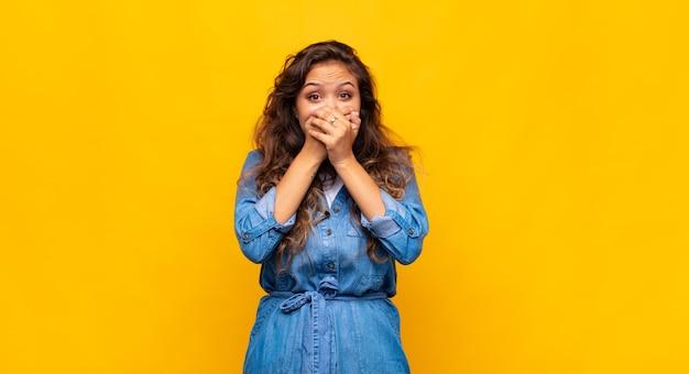 黄色の壁にポーズをとって表現力豊かな若い女性