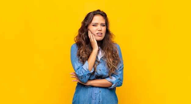 Young expressive woman posing on yellow wall