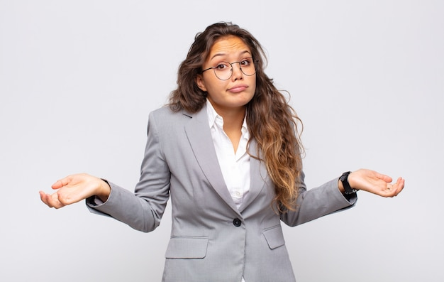 Молодая выразительная женщина в очках и элегантном костюме позирует на белой стене