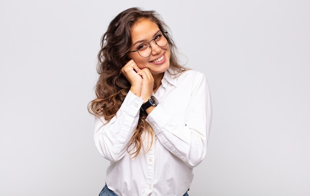 Young expressive woman with glasses and elegant white blouse posing on white wall