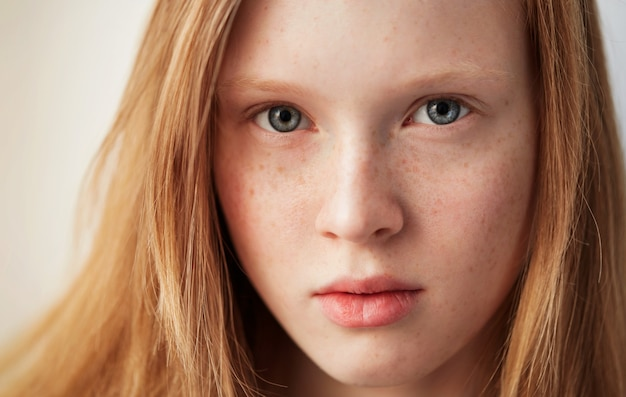 Young eyes girl beautiful redhead freckles woman face closeup portrait with healthy skin