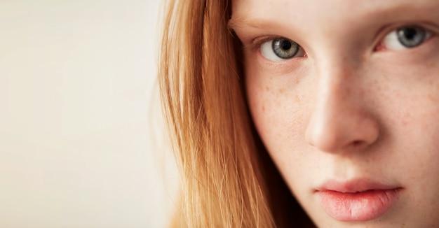 Молодые глаза девушка красивая рыжая веснушки женщина лицо крупным планом портрет со здоровой кожей