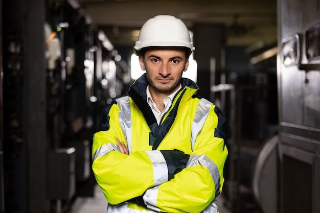 Young factory engineer or worker wearing safety vest and hard hat crossing arms at electrical room