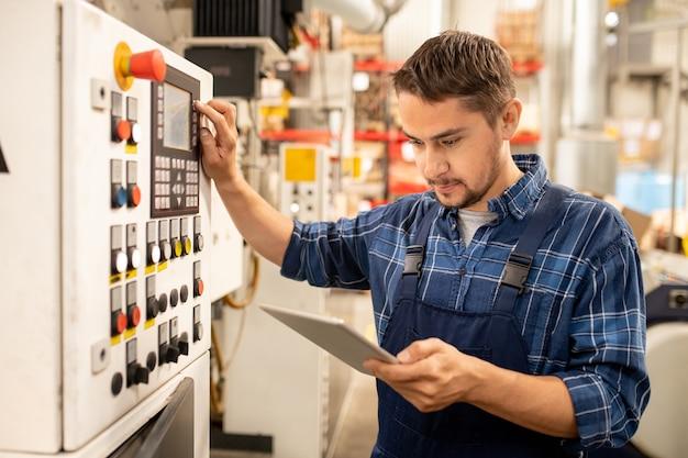コントロールパネルで作業パラメーターを選択しながらオンラインの指示を見る若い工場技術者