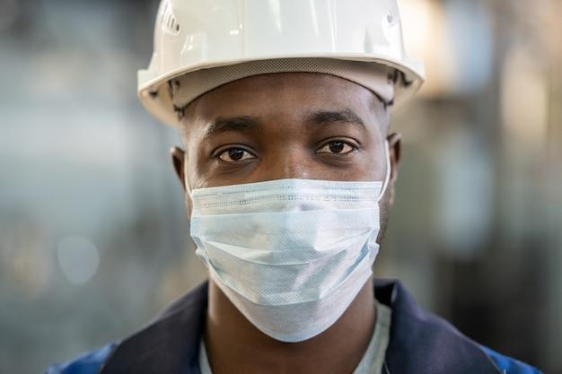 작업복, 안전모, 보호용 마스크를 쓴 아프리카 민족의 젊은 공장 노동자가 카메라 앞에 서서 당신을 바라보고 있습니다.