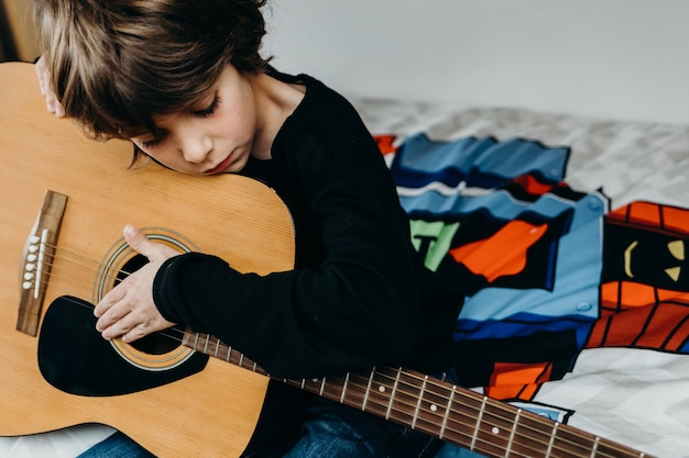 Young fair-haired boy sitting on the bed and holding a guitar