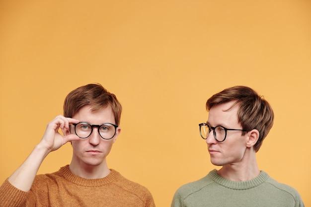 오렌지 배경에 안경을 조정하는 형제를 바라보는 올리브 스웨터를 입은 젊은 공정한 남자