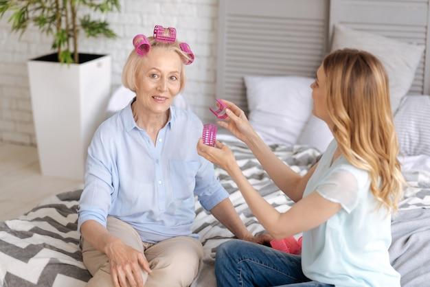 양손에 머리 롤러를 들고 젊은 fair-haired 여자는 침대에 앉아 정면에서 웃고있는 그녀의 어머니의 머리카락에 그들을 고치려고합니다.