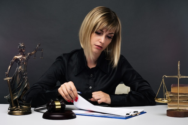 A young fair woman judge works in her office.