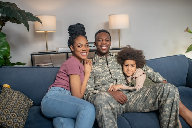Young family. african american little smiling girl man in military uniform and woman with hairstyle sitting together on sofa at home