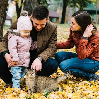 Young family and cat in park with autumn foliage