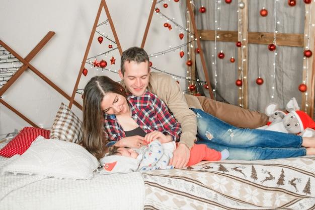 Молодая семья на рождество. счастливая семья мама папа и ребенок