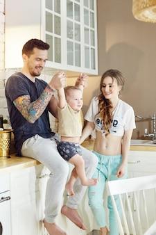 休日の朝に家にいる若い家族。夫婦と彼女の腕の中で彼らの小さな赤ちゃん。うれしそうな幸せそうな顔を抱き締めて楽しんでいます