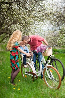 Young family on a bicycles in the spring garden