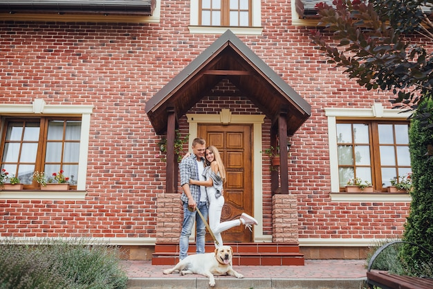 Young family bought a new home. attractive men and woman with labrador near the big house. couple looking at the camera.