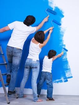若い家族が一緒に壁を青い色に磨きます