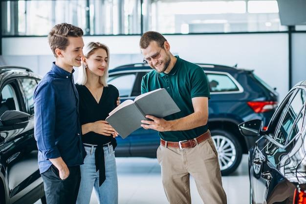 Молодая семья покупает машину в автосалоне
