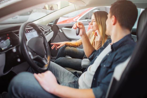 ショールームで最初の電気自動車を買う若い家族。彼の妻が豪華な環境に優しい車のダッシュボードのデザインを見て、車のキーを押しながらステアリングホイールの後ろに魅力的な男。