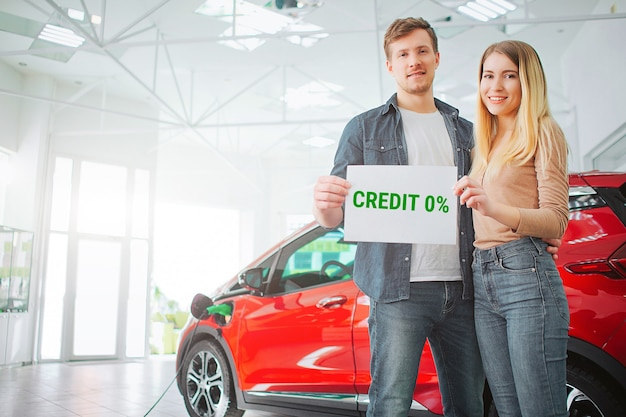 Young family buying first electric car in the showroom. smiling attractive couple holding paper with word credit while standing near eco red vehicle. battery electric car for ecology.
