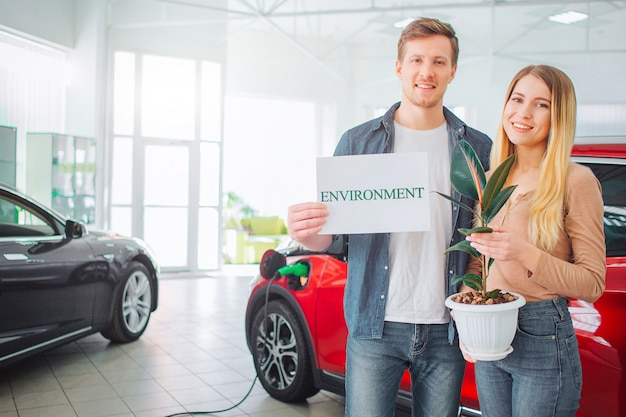 Young family buying first electric car in the showroom. smiling attractive couple holding paper with word environment and flowerpot while standing near eco red vehicle. green car concept
