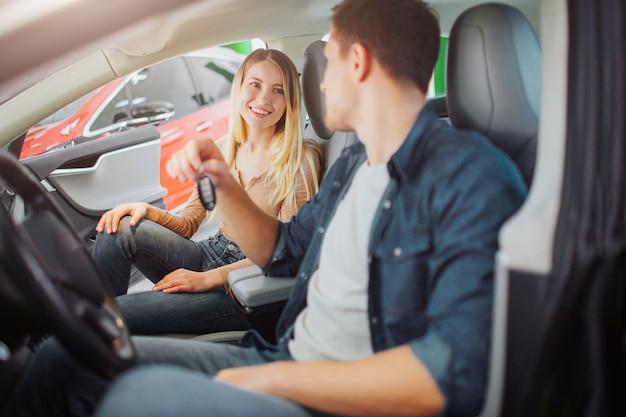 Молодая семья покупает свой первый электромобиль в автосалоне