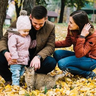 Giovane famiglia e gatto nel parco con fogliame autunnale