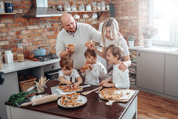 Young family of caucasian people taste and eat pizza they have cooked and enjoy their holidays.