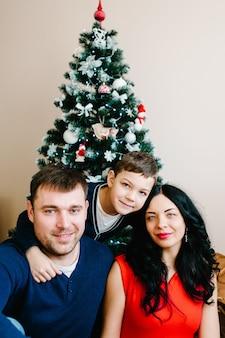 クリスマスツリーの近くで自宅でクリスマスを祝う若い家族。幸せなママ、パパと息子が一緒に休日の時間を楽しんでいます。