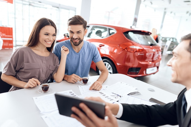 A young family choose a new car in the car showroom