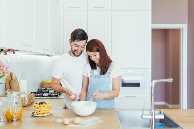Молодая семья вместе готовит завтрак на красивой белой кухне