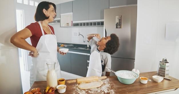 Молодая семья готовит еду на кухне. счастливая маленькая девочка с жидким тестом ее матери смешивая. мать и маленький мальчик готовят тесто. счастливая семья на кухне и младший повар концепции.