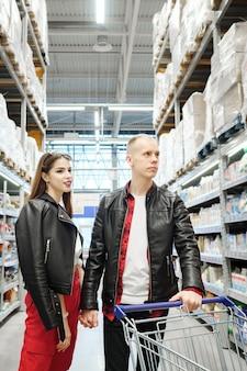 毎週の買い物、クローズアップ中にスーパーマーケットで食べ物を選ぶ若い家族のカップル