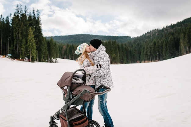 Young family couple kiss, near baby stroller on snow in carpathian mountains. on background of forest and ski slopes. close up.