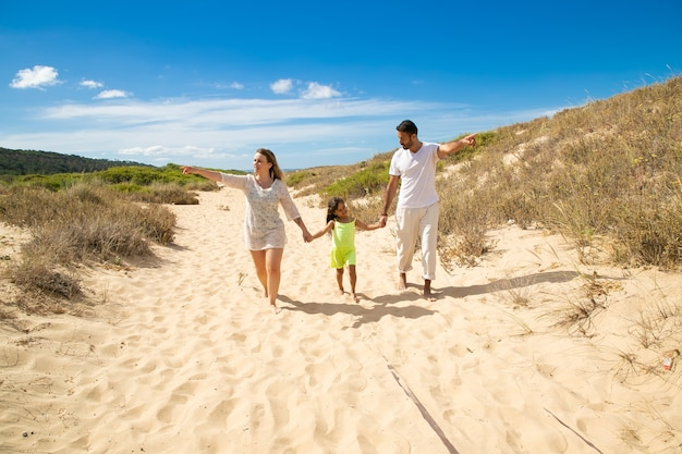 Young family couple and little kid in summer clothes walking white along sand path, pointing hands away, girl holding parents hands
