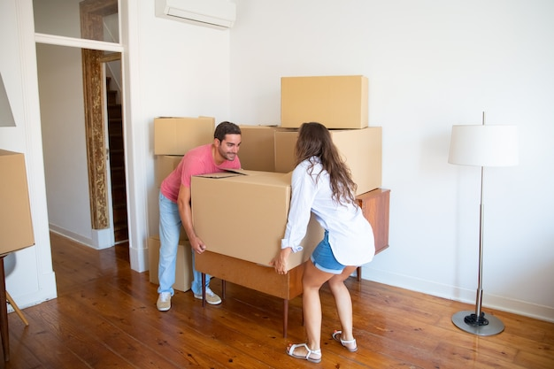 Young family couple moving into new apartment, carrying carton boxes and furniture