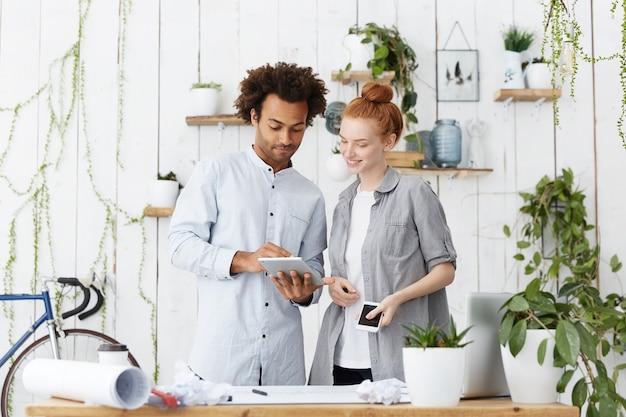 Молодая семейная пара смешанной расы делает проекты своего будущего дома