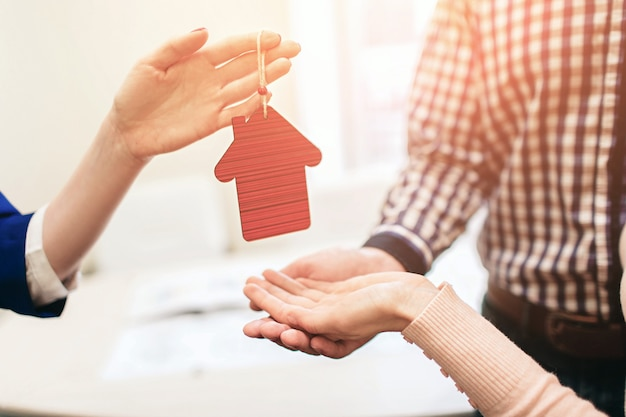 Young family couple purchase rent property real estate . agent giving consultation to man and woman. signing contract for buying house or flat or apartments. he holds a model of the house in hands.
