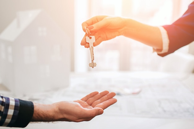 Young family couple purchase rent property real estate . agent giving consultation to man and woman. signing contract for buying house or flat giving keys to couple of customers. close up.