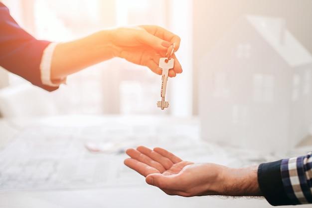 Молодая семейная пара приобретает в аренду недвижимость. агент дает консультации мужчине и женщине. подписание договора на покупку дома или квартиры. передача ключей нескольким покупателям. закройте вверх.