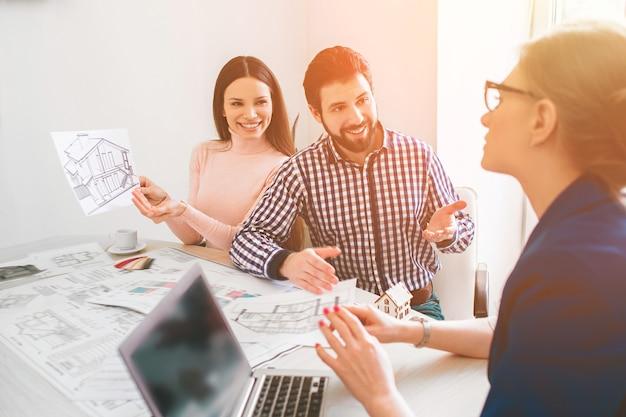 젊은 가족 부부 구매 임대 부동산 부동산. 남자와 여자에게 상담을 제공하는 에이전트. 주택, 아파트 또는 아파트 구매 계약 체결. 크기에 대한 논의.