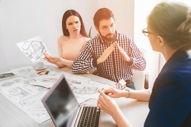 젊은 가족 부부 구매 임대 부동산 부동산. 남자와 여자에게 상담을 제공하는 에이전트. 주택, 아파트 또는 아파트 구매 계약 체결.