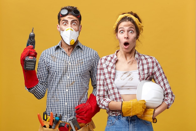Молодая семейная пара в защитной одежде во время ремонта в своей квартире держит дрель и каску с удивленным взглядом, испуганными делать много работы с грязными лицами