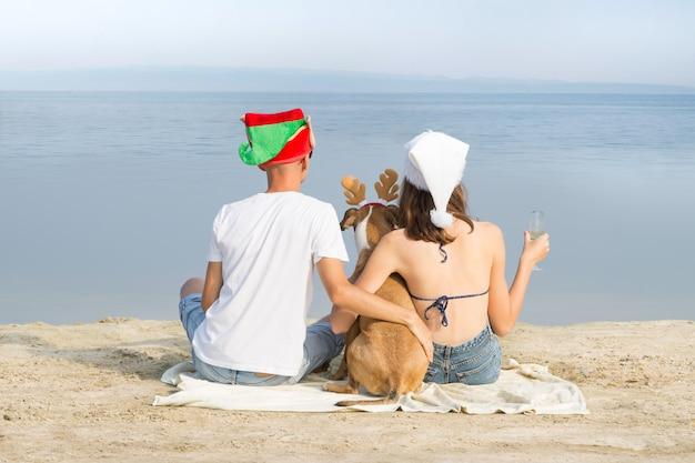 애완 동물 강아지와 함께 젊은 가족 부부는 해변에 앉아 크리스마스 휴가 바다 전망을 즐길 수