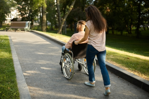 Young family couple with wheelchair walking in the park. paralyzed people and disability, care for a disabled man. husband and wife overcome difficulties together