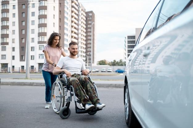 Молодая семейная пара с инвалидной коляской, идущей к машине. парализованный ветеран и инвалид, уход за инвалидом. муж и жена вместе преодолевают трудности
