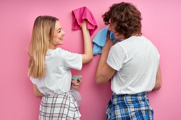 若い家族は一緒に家事をし、コンセプトを掃除します。カジュアルな家庭用ウェアのフレンドリーなカップルは、自宅で衛生的な仕事をしています。