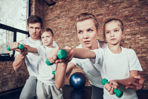 Young family doing exercises with dumbbells.