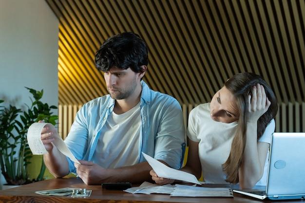 집에서 서류를 하 고 젊은 가족 종이 문서가 많은 테이블에 앉아 걱정 찾고 젊은 부부